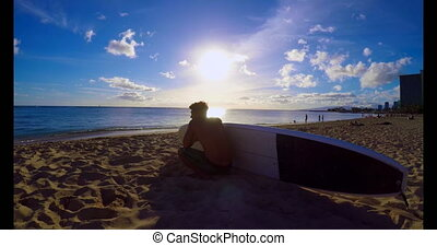 Surfer with a surfboard sitting on the beach 4k - Rear view...