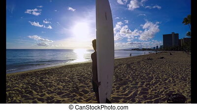 Surfer with a surfboard standing on the beach 4k - Side view...