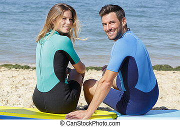 surfers couple looking at the camera