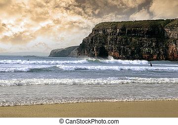 surfers near cliffs before a storm