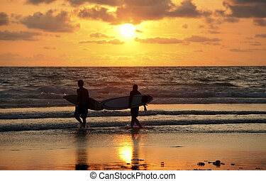 Surfers on sunset - Silhouettes of three surfers at red...