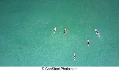 surfers sail on surfboards among rippling water