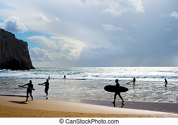 Surfers silhouette surfboards beach Portugal