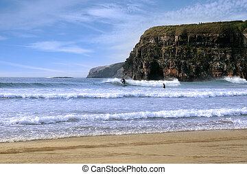surfers surfing near ballybunion cliffs