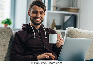 Surfing net at home. Cheerful young man using his laptop and looking at camera with smile while sitting on couch at home