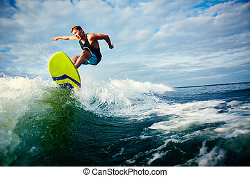Surfing - Male surfer riding on waves in the sea