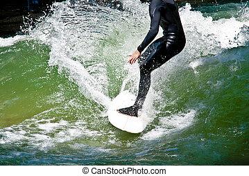 Surfing - Surfer in a black neoprene suit on a surfing board...