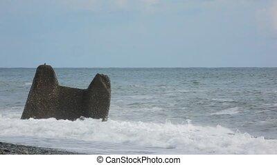 surfing waves of sea break against the rock in pebble beach
