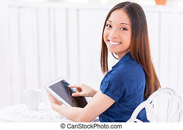 Surfing web in cafe. Rear view of beautiful young Asian woman using digital tablet and looking over shoulder while sitting in cafe