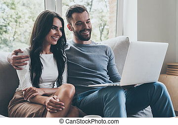 Surfing web together. Beautiful young loving couple looking at laptop and smiling while sitting together on the couch
