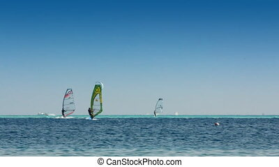 surfing - windsurfers and kitesurfer on blue sea surface