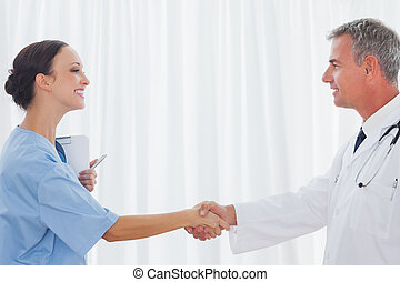 Surgeon and doctor shaking hands