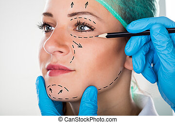 Surgeon Drawing Lines On Woman's Face For Plastic Surgery -...