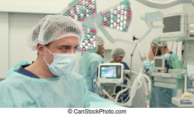 Surgeon finishes surgery - Close up of young surgeon...