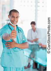 Surgeon gesturing thumbs up with group around table in hospital