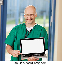 Surgeon Holding Laptop In Clinic