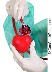 Surgeon listening to a plastic heart with a stethoscope