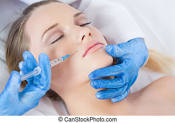 Surgeon making injection above lips on woman lying