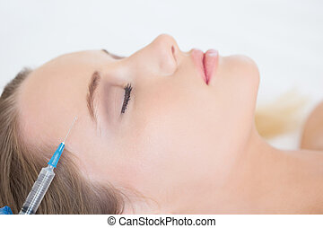 Surgeon making injection on content woman lying