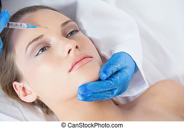Surgeon making injection on forehe