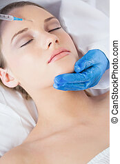 Surgeon making injection on forehead on peaceful woman lying