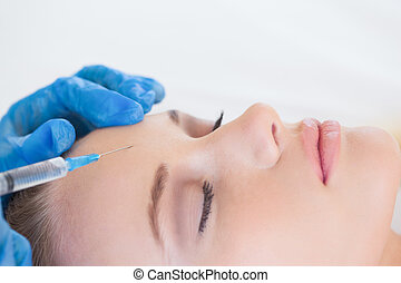 Surgeon making injection on natural woman lying