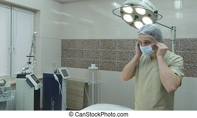 Surgeon putting his mask in an operating theatre.