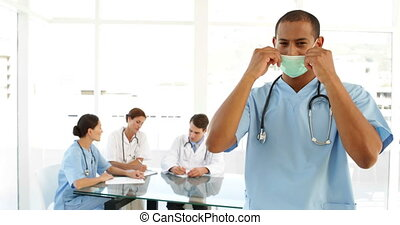 Surgeon taking off his protective mask