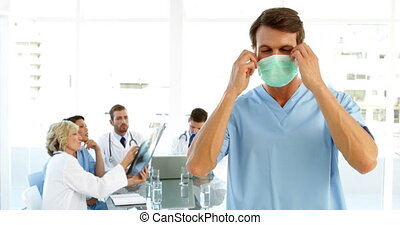 Surgeon taking off mask with staff talking behind him at the...