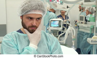 Surgeon touches his beard - Middle aged surgeon touching his...