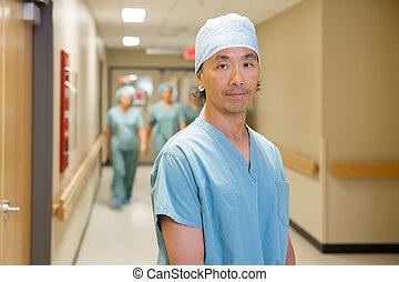 Surgeon With Team Walking In Hospital Corridor