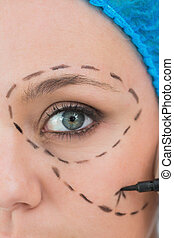 Surgeon writing on a woman's face