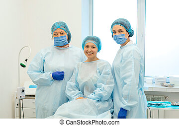 surgeons and happy patient after successful surgery to remove a mole on the back