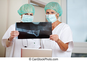 Surgeons Looking At Xray In Clinic - Female surgeons looking...