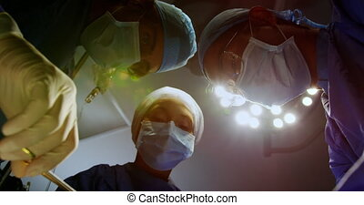 Low angle view of surgeons performing operation in operation theater at hospital. They are holding surgical instruments 4k