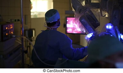 Surgeons - Surgeon operating a robotic surgery machine