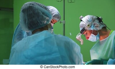 Surgeons wearing protective clothing performing surgery...