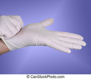 Surgical gloves - Hands putting on surgical gloves over a...