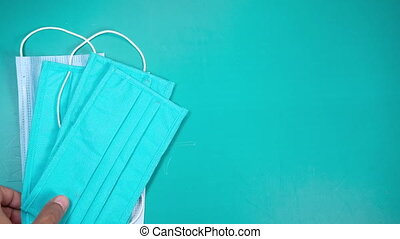 Surgical masks, gloves and hand sanitizer on green background ,