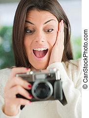 surpris, femme regarde, appareil-photo