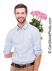 Surprise for her. Handsome young man hiding a bouquet with pink roses behind back and smiling while standing isolated on white background