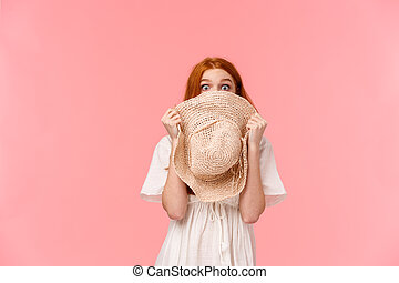Surprise, look at camera. Shy and blushing cute startled redhead girl hiding face behind straw hat, staring camera scared or shook, standing pink background overwhelmed.