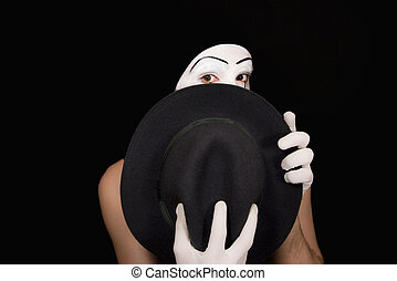 Surprise mime with a hat on a black background