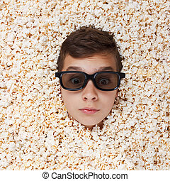 Surprise young boy in stereo glasses looking out of popcorn...