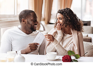 Surprised African American woman receiving a present from her boyfriend