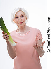 Surprised aged woman holding leek in right hand - It is your...
