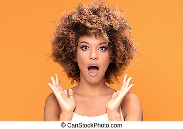 Surprised amazed beautiful afro woman with wide open mouth.