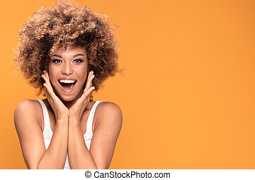 Surprised amazed beautiful afro woman with wide open smiling mouth.