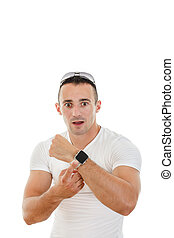 confused handsome man in white t-shirt pointing a finger at cloc