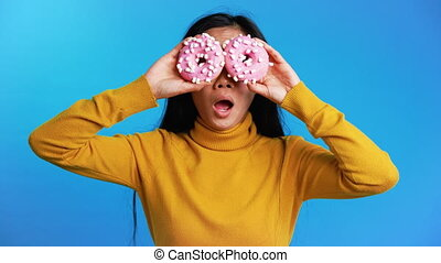 Surprised asian woman showing doughnuts in front of her eyes...